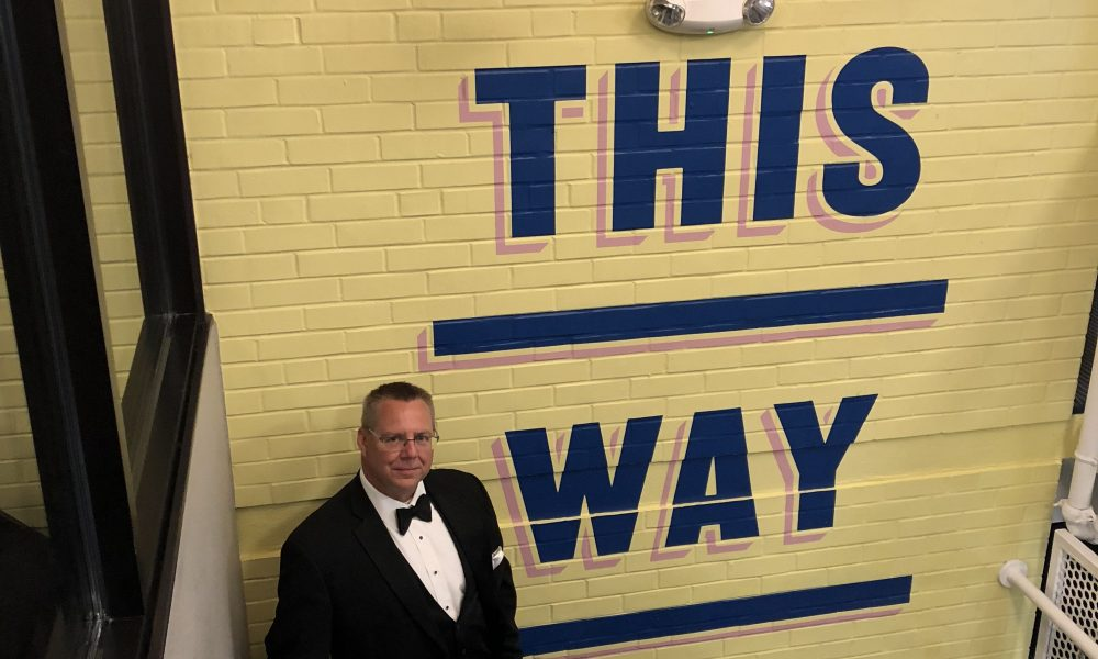 Jamie standing in a tuxedo in a stairwell. The wall says walk this way
