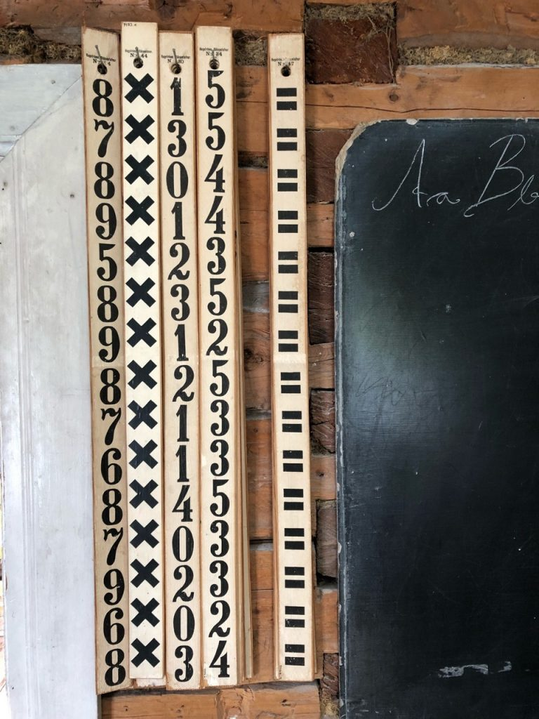 Arithmetic help in a 100+ year old one-room school house! What do these also make you think of? Napier's bones? Other multiplication strategies with lines or pieces of paper? Why do some sticks appear to have random numbers from a small range of values? (Västerbotten Museum, Umea, Sweden)